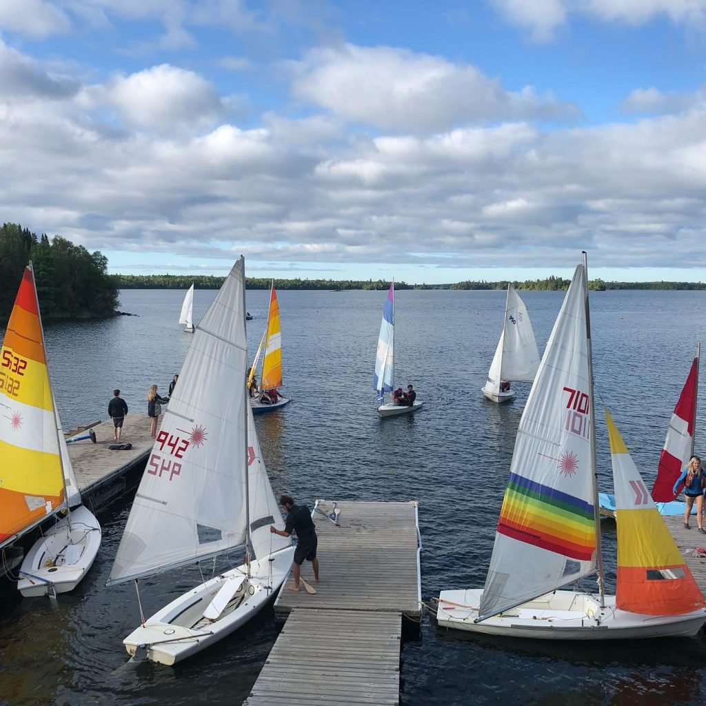 Campers sailing on a lake close to Pioneer Camp Manitoba